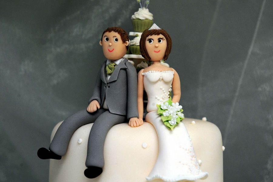 General view of bride and groom cake decorations on a wedding cake at Delicious - Dishes, Swadlincote.