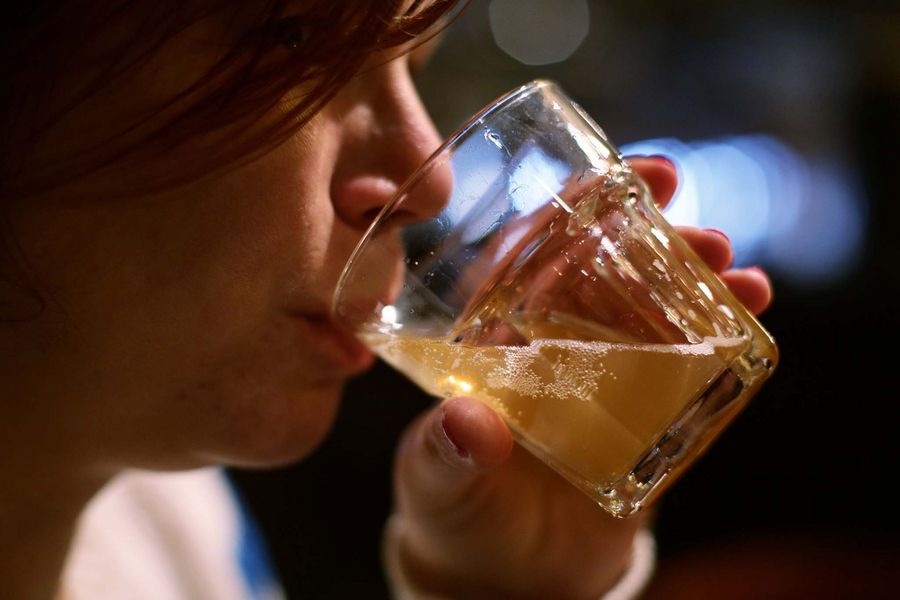 File photo dated 07/02/16 of a woman drinking a glass of beer in a pub, as a survey shows the number of pub and bar companies going insolvent has fallen by 7\% over the past year amid increased popularity of craft beers and food.