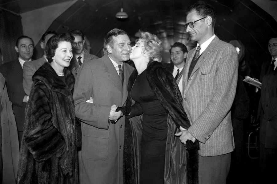 Hollywood Actress Marilyn Monroe (second from right) greets English actor Sir Laurence Olivier with a kiss on the cheek, watched by his wife Vivien Leigh (l) and Monroe's husband Arthur Miller (r). Marilyn Monroe was in Britain to star in 'The Sleeping Prince' with Sir Laurence Olivier.
