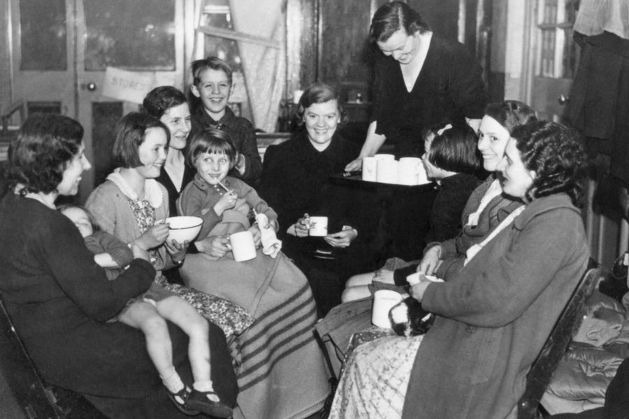 A group of East End evacuees enjoy refreshments in their emergency quarters, while waiting for new accommodation.